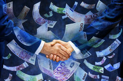 Euros Euro Handshake Venture Money Capital. Two businessmen shaking hands with Euro notes raining down Stock Photography