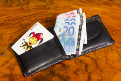 Euros with joker card in wallet, on vintage brown Royalty Free Stock Photography