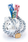 Euros in padlocked piggy bank. Euros in slot of piggy bank or money box secured with padlock and isolated on white background