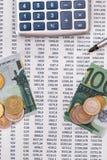 100 euros rasgados, calculadora, pluma con las monedas Foto de archivo libre de regalías