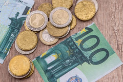 100 euros rasgados con las monedas Imagen de archivo libre de regalías