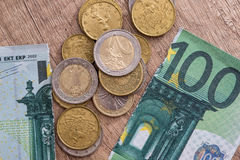 100 euros rasgados con las monedas Fotografía de archivo