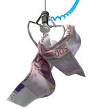 Euros In A Robotic Claw. An robotic claw from an arcade type game gripping a wad of creased euro notes on an isolated white background Royalty Free Stock Photography