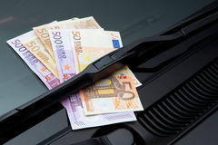 Euros under windshield wiper. Euros stuck under a windshield wiper symbolizing car expenses Stock Images