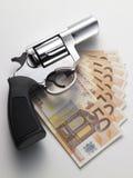 Eurosedel och revolver Arkivfoto