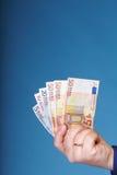 Eurosedlar i den manliga handen Arkivfoto