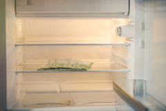 Eurosedlar i ett tomt kylskåp: en handfull 100 eurosedlar i ett tomt kylskåp Kvinnliga handtagandepengar från fri Arkivfoto