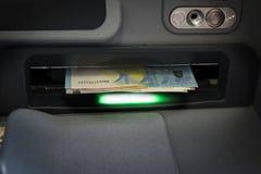 Eurosedlar i springan av en atm, ordnar till för att ta ut, bland t arkivfoton