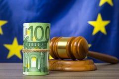 Eurosedlar med en trädomstolauktionsklubba mot europeisk facklig flagga som ett begrepp av korruption i rättsväsendet royaltyfria bilder