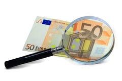 Eurosedlar med ett förstoringsglas Arkivbild