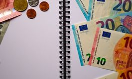 Eurosedlar, mynt på en vit notepad royaltyfria foton