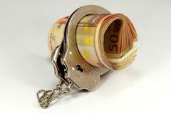 Eurosedlar och handbojor Arkivfoto