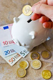 Eurosedlar och mynt med spargrisen Arkivfoto