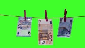 Eurosedlar på kläderlinje grön skärm arkivfilmer