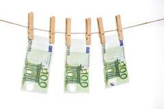 100 eurosedlar som hänger på klädstreck på vit bakgrund Arkivbild