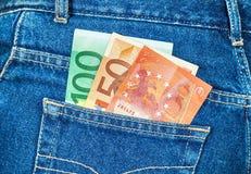 Eurosedlar som klibbar ut ur den tillbaka jeansen, stoppa i fickan Arkivfoto