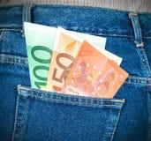 Eurosedlar som klibbar ut ur den tillbaka jeansen, stoppa i fickan Royaltyfri Bild