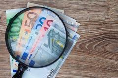 Eurosedlar under seende exponeringsglas Arkivbilder