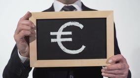 Eurosymbol gezeichnet auf Tafel in den Geschäftsmannhänden, europäische Währung, Finanzierung stock footage