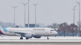 Eurowings Airbus doing taxi on Munich Airport runway. Eurowings plane landed on runway, snowy runways stock footage