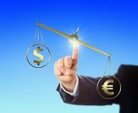 Eurozeichen, das den Dollar auf einer Balance überwiegt Lizenzfreie Stockbilder