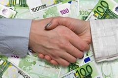 Eurozone deal concept. Business handshake on euros background Stock Photos
