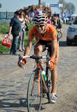 Euskaltel rider in Paris Roubaix. A little Euskaltel rider (Alan Perez) riding on the cobblestones of Gruson in Paris Roubaix 2011 Stock Images
