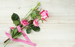 Eustoma and roses on wooden surface Stock Images