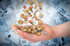 Euzro coins falling in open hand. Euro coins money rain falling in open hand in front of banknote background financial business success concept Stock Image