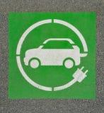 EV - знак зарядной станции электротранспорта на асфальте Знак ` ` e на предпосылке асфальта стоковые изображения