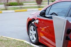 EV-bil eller elektrisk r?d bil p? uppladdningsstationen med tillf?rselen f?r maktkabel som pluggas in p? den suddiga naturen med  arkivfoto
