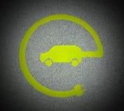 EV - sinal da estação de carregamento do veículo elétrico Sinal do ` do ` E na textura do asfalto imagens de stock royalty free