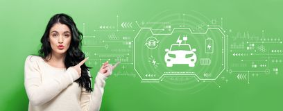 EV with young woman. Pointing on a green background stock image