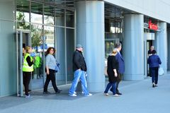 Free Evacuation Of An Office Building. People Exit The Building On Exit Door. Stock Photography - 142307772