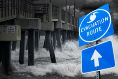 Evacuation route from a hurricane. An evacuation route sign in front of a windy pier stock photo