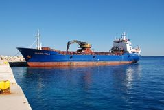 Evagelistria Skopelou, Alonissos. Freight ship Evagelistria Skopelou unloads at Patitiri harbour on the Greek island of Alonissos. The ship was built in Norway royalty free stock photography
