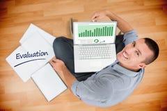 Evaluación contra el hombre de negocios creativo joven que trabaja en el ordenador portátil Foto de archivo libre de regalías