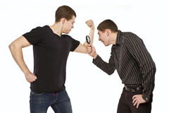 Evaluate. A guy with a magnifying glass considers triceps of his friend Royalty Free Stock Images