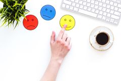 Evaluate customer service. Hand point emoji smiling, neutral, sad face on work desk on white background top view copy. Evaluate customer service. Hand point royalty free stock images