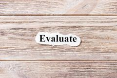 Evaluate of the word on paper. concept. Words of Evaluate on a wooden background.  Stock Image