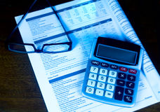 Evaluating a 401k with calculator and eyeglasses. Royalty Free Stock Image