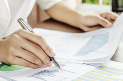 Evaluating data. Woman evaluating charts and documents on paper Royalty Free Stock Photography