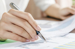 Evaluating data. Woman evaluating charts and documents on paper Royalty Free Stock Photo