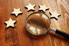 Evaluation and assessment. Five stars and magnifying glass. Evaluation and assessment concept. Five stars and magnifying glass royalty free stock images