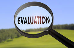 Evaluation. Magnifying glass with the word evaluation on blurred nature background Stock Photo