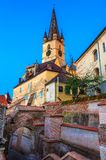 Evanghelical Church in Sibiu. Evanghelical Church's famous tower, landmark of Sibiu, with a medieval street and some of the old town fortification walls Royalty Free Stock Photos