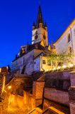 Evanghelical Church in Sibiu. Evanghelical Church's famous tower, landmark of Sibiu, with a medieval street and some of the old town fortification walls Stock Photos