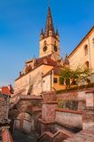 Evanghelical Church in Sibiu. Evanghelical Church's famous tower, landmark of Sibiu, with a medieval street and some of the old town fortification walls Stock Image