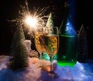 Eve Новые Годы предпосылки торжества с парами каннелюр и бутылки шампанского с рождественской елкой на снеге на темной предпосылк Стоковые Изображения RF