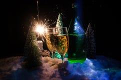 Eve Новые Годы предпосылки торжества с парами каннелюр и бутылки шампанского с рождественской елкой на снеге на темной предпосылк Стоковая Фотография